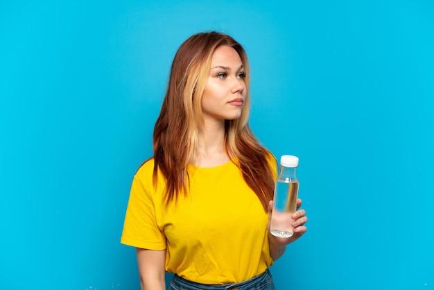 Nastoletnia dziewczyna z butelką wody na odosobnionym niebieskim tle, patrząc w bok