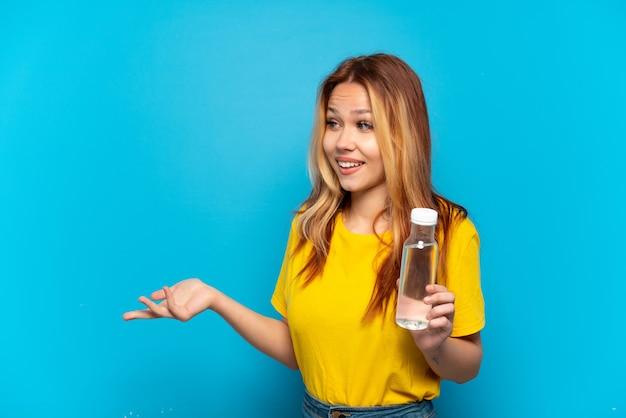 Nastoletnia dziewczyna z butelką wody na odosobnionym niebieskim tle z wyrazem zaskoczenia, patrząc z boku