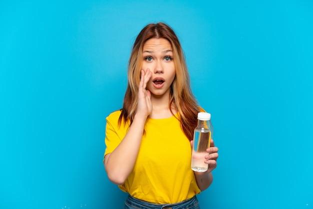 Nastoletnia dziewczyna z butelką wody na odosobnionym niebieskim tle z zaskoczeniem i zszokowanym wyrazem twarzy facial