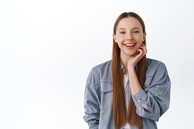 Nastoletnia dziewczyna z czystą idealną skórą dotyka policzka i uśmiecha się szczęśliwie, pozbyła się trądziku, koncepcja leczenia po kosmetykach, stojąc zadowolona na białej ścianie.
