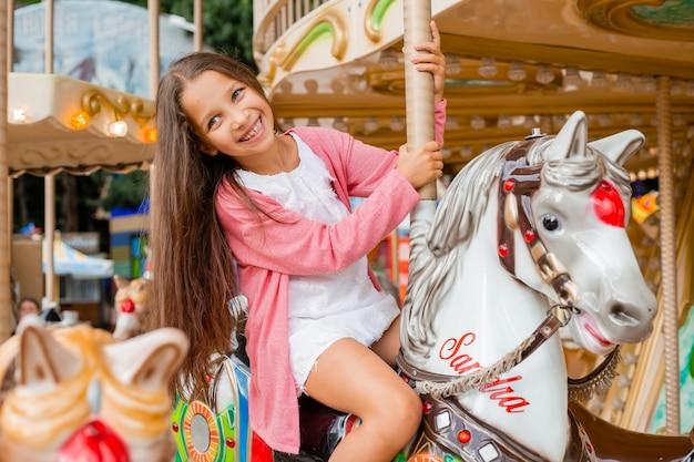 Nastoletnia dziewczyna z długimi włosami toczy się na karuzeli z huśtawką. siedząc na koniu w wesołym miasteczku