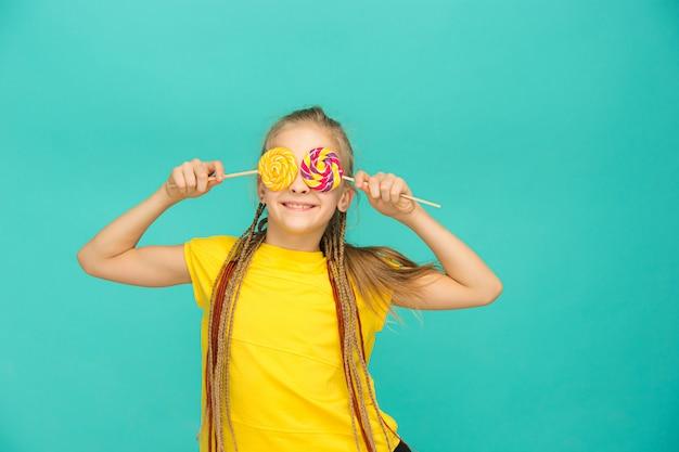 Nastoletnia dziewczyna z kolorowym lizakiem na błękicie