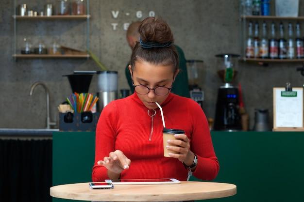 Nastoletnia dziewczyna z pastylką siedzi w kawiarni.