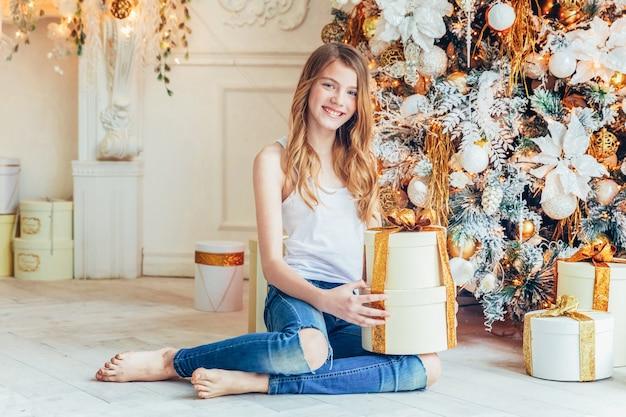 Nastoletnia dziewczyna z prezenta pudełkiem blisko choinki w wigilię bożego narodzenia w domu. młoda kobieta w lekkim pokoju z zimową dekoracją. czas bożego narodzenia na koncepcji uroczystości