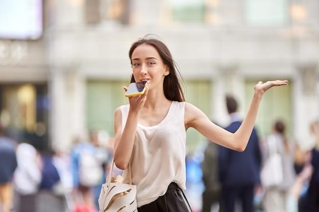 Nastoletnia dziewczyna z telefonem komórkowym stoi na ulicy miasta i rozmawia