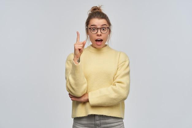 Nastoletnia dziewczyna, zszokowana kobieta o blond włosach zebranych w kok. ubrany w żółty sweter i okulary. podnosząc palec wskazujący, mam pomysł. patrząc w kamerę, na białym tle nad białą ścianą