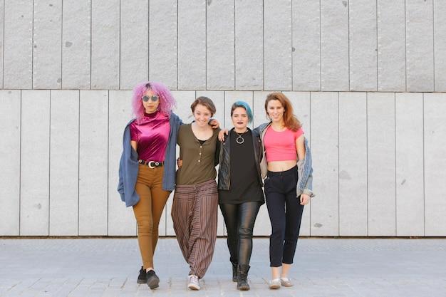 Nastoletnia grupa kobiet ściska i chodzi na ulicie