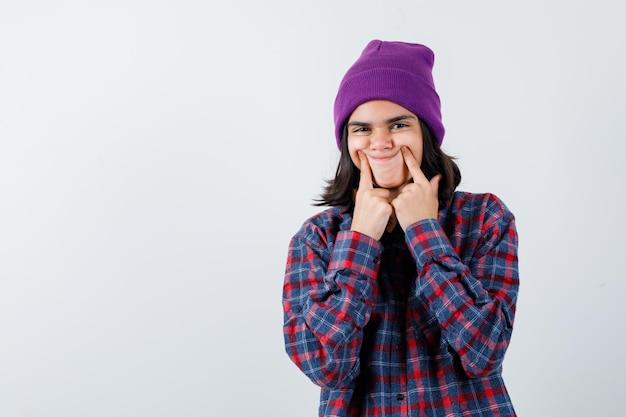 Nastoletnia kobieta kładzie palec wskazujący w pobliżu ust, zmuszając się do uśmiechu