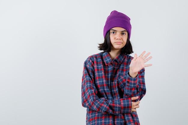 Nastoletnia kobieta machająca ręką na powitanie w kraciastej fioletowej czapce wyglądającej przyjaźnie