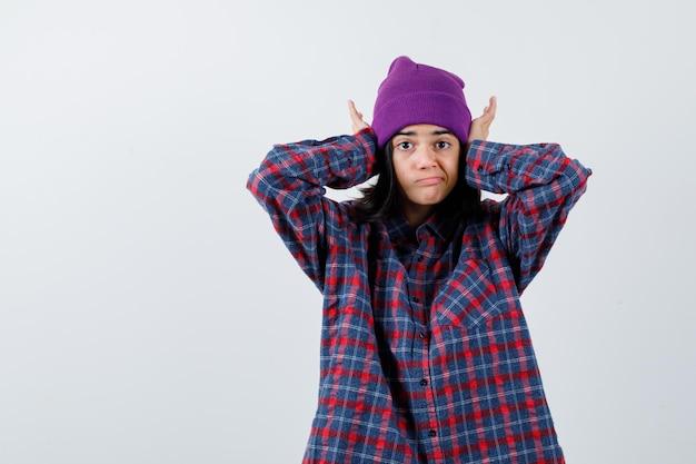 Nastoletnia kobieta naciskająca ręce na uszy w kraciastej fioletowej czapce wygląda na zirytowaną