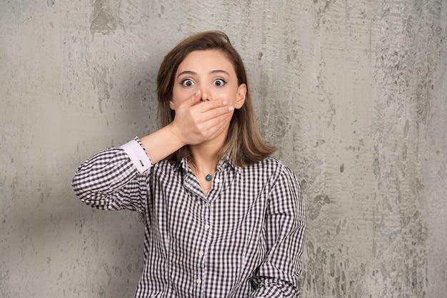 Nastoletnia kobieta obejmująca usta ręką na szarej ścianie