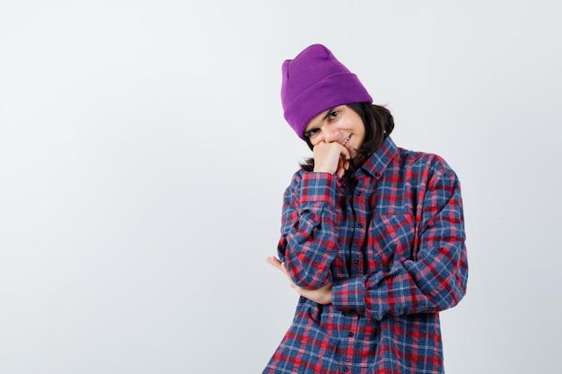 Nastoletnia kobieta opierając policzek na dłoni w kraciastej koszuli i czapce wyglądającej wesoło