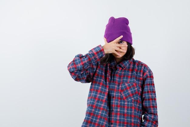 Nastoletnia kobieta patrząca przez palce czapka wyglądająca na zdziwioną
