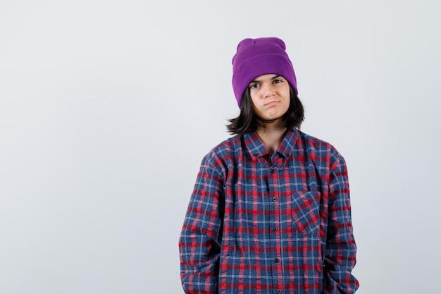 Nastoletnia kobieta patrzy na czapkę z kamerą, patrząc ostrożnie