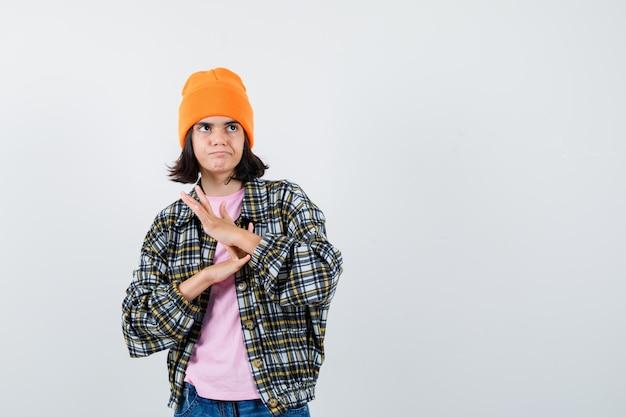 Nastoletnia kobieta pociera dłonie w czapce z t-shirtem i wygląda na zamyśloną