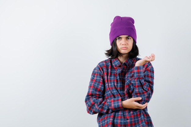 Nastoletnia kobieta podnosi rękę w zdziwiony sposób czapka wyglądająca na zdezorientowaną