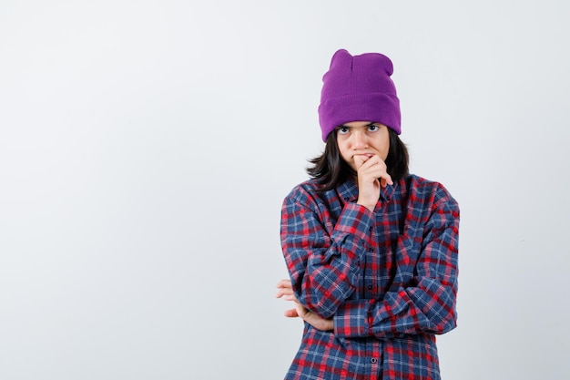 Nastoletnia kobieta podpierająca podbródek na czapce z zamyśloną miną