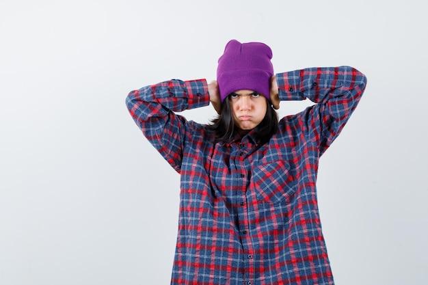 Nastoletnia kobieta trzymająca ręce na uszach, dmuchając w policzki, wyglądając na znudzoną