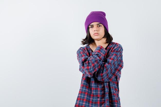 Nastoletnia kobieta trzymająca się za ręce na gardle w kraciastej koszuli i czapce wygląda na zmęczoną