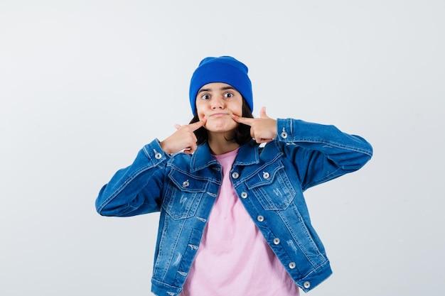 Nastoletnia kobieta umieszczająca palce wskazujące w pobliżu ust, zmuszając się do uśmiechu w różowej koszulce wyglądającej uroczo