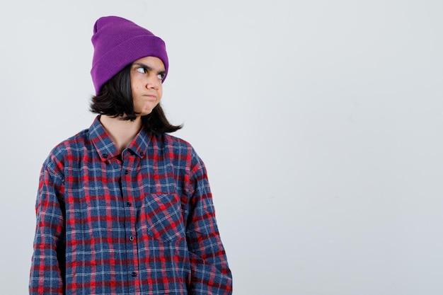Nastoletnia kobieta w kraciastej koszuli fioletowa czapka odwracająca wzrok