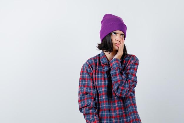 Nastoletnia kobieta w kraciastej koszuli i czapce odciąga powiekę i wygląda na znudzoną