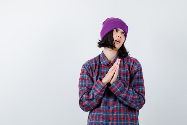 Nastoletnia kobieta w kraciastej koszuli i czapce trzymająca się za ręce w geście modlitwy