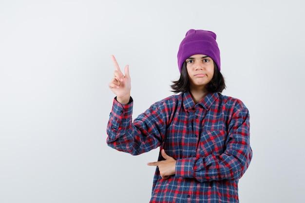 Nastoletnia kobieta w kraciastej koszuli i czapce, wskazując w górę i patrząc uważnie