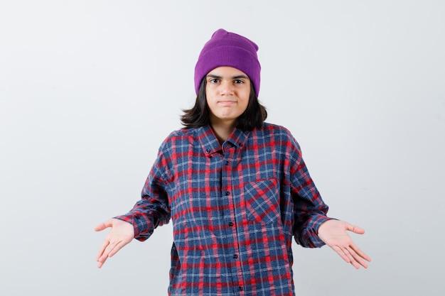 Nastoletnia kobieta w kraciastej koszuli i fioletowej czapce pokazująca bezradny gest