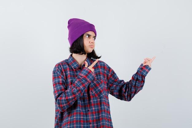 Nastoletnia kobieta w kraciastej koszuli i fioletowej czapce wskazującej w prawo, patrząc na skoncentrowaną