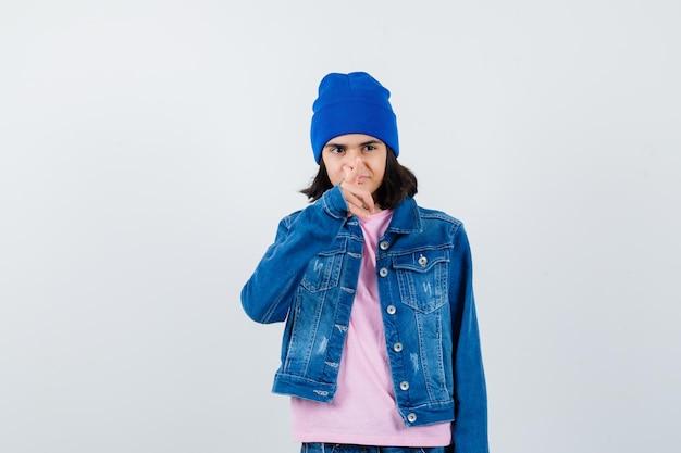Nastoletnia kobieta wskazująca na aparat palcem wskazującym w różowej koszulce, która wygląda na skupioną