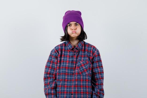 Nastoletnia kobieta wydmuchująca policzki w kraciastej koszuli i czapce wygląda na znudzoną
