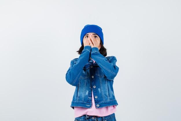 Nastoletnia kobieta zakrywająca usta dłońmi wygląda na podekscytowaną
