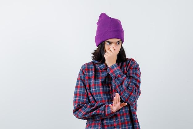 Nastoletnia kobieta zakrywająca usta ręką pokazującą znak stop w kraciastej koszuli wygląda poważnie