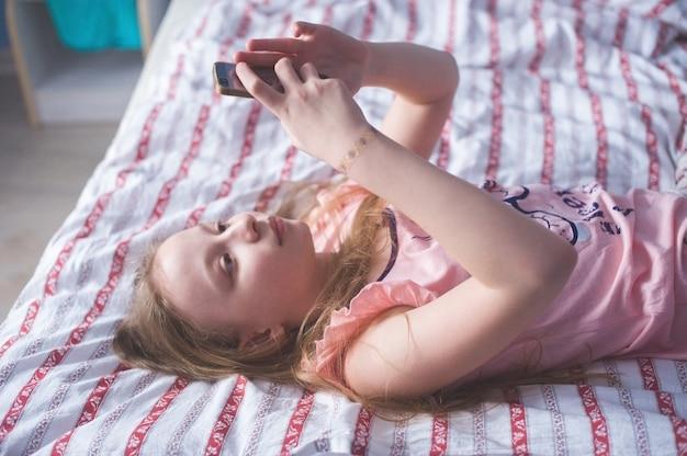Nastoletnia leżąca na łóżku z tyłu i patrzy w telefon