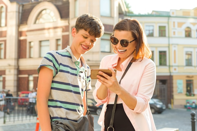 Nastoletnia matka i syn patrzą na telefon komórkowy