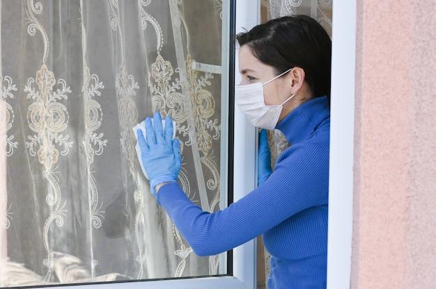 Nastoletnia młoda kobieta myje okno maską