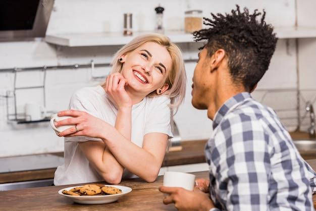 Nastoletnia para trzyma kubek w ręku siedzi razem o śniadanie