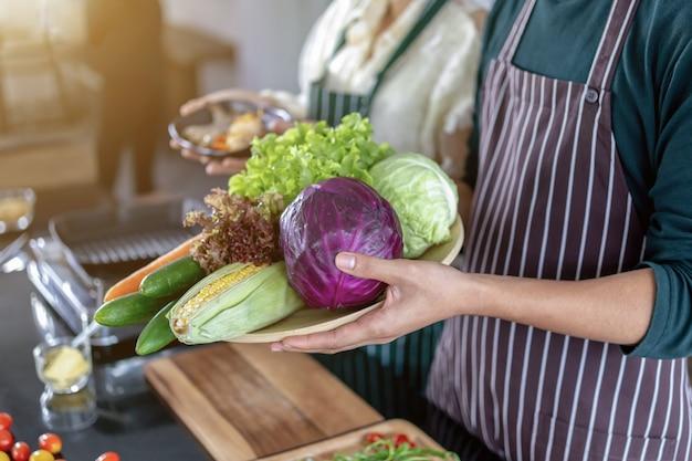 Nastoletnia pokazuje garnela i warzywa w kuchni