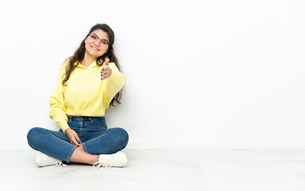 Nastoletnia rosjanka siedzi na podłodze, ściskając ręce, żeby zamknąć dobrą ofertę