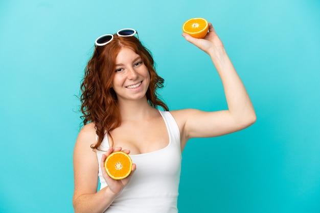 Nastoletnia ruda dziewczyna na białym tle na niebieskim tle w stroju kąpielowym i trzymająca pomarańczę