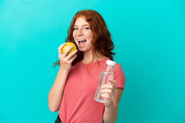Nastoletnia ruda dziewczyna na białym tle na niebieskim tle z butelką wody i jedzeniem jabłka