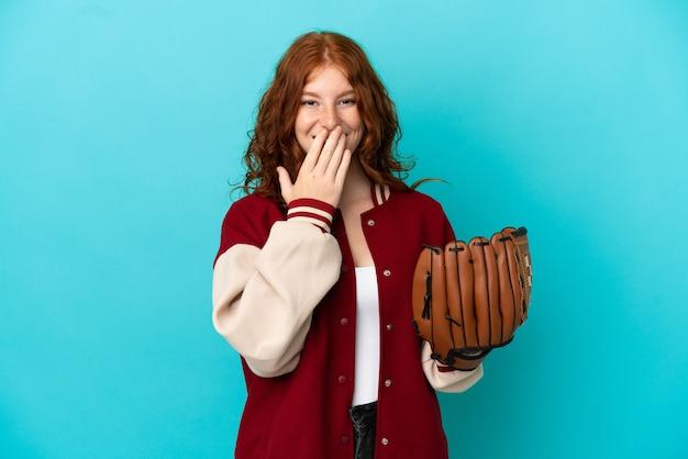 Nastoletnia ruda dziewczyna z rękawicą baseballową na niebieskim tle szczęśliwa i uśmiechnięta zakrywająca usta dłonią