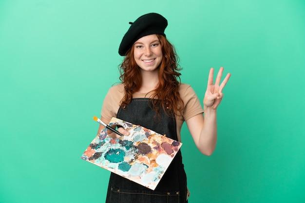 Nastoletnia rudowłosa artystka trzymająca paletę na białym tle na zielonym tle szczęśliwa i licząca trzy palcami
