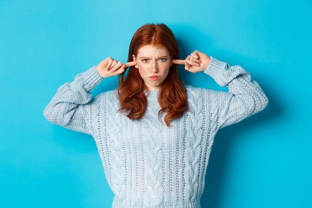 Nastoletnia rudowłosa dziewczyna nie chce słuchać, zamyka uszy i marszczy brwi w złości, wpatruje się w obrażoną kamerę, dąsa się na niebieskim tle