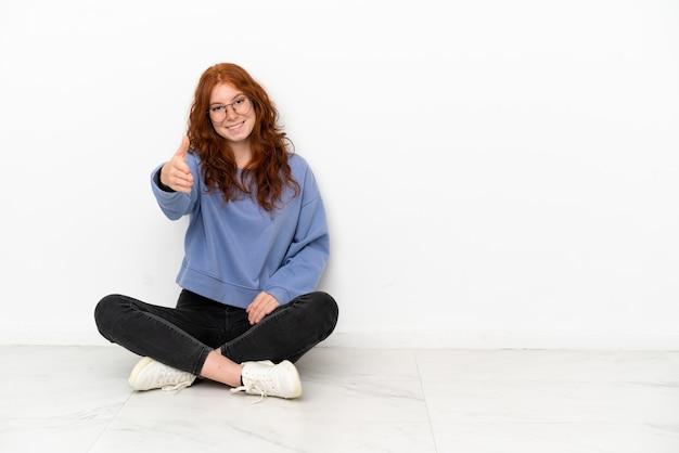 Nastoletnia rudowłosa dziewczyna siedzi na podłodze na białym tle, ściskając ręce, aby zamknąć dobrą ofertę