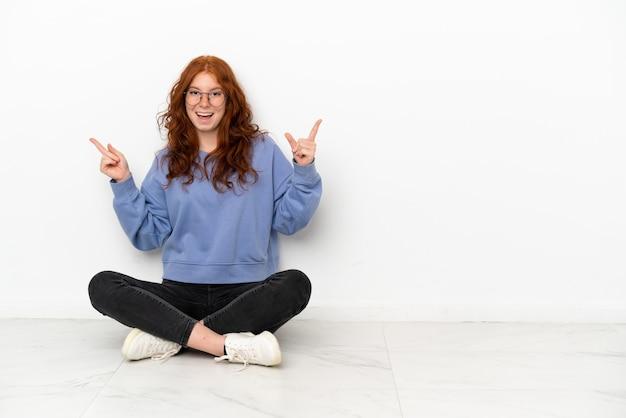Nastoletnia rudowłosa dziewczyna siedzi na podłodze na białym tle, wskazując palcem na boki i szczęśliwa