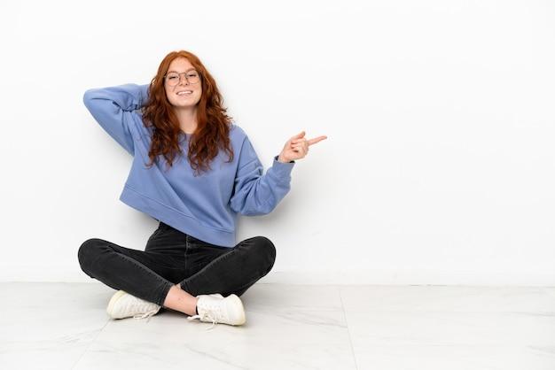 Nastoletnia rudowłosa dziewczyna siedzi na podłodze na białym tle zaskoczona i wskazując palcem w bok