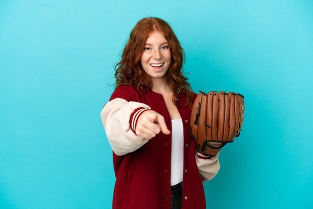 Nastoletnia rudowłosa dziewczyna z rękawicą baseballową na białym tle na niebieskim tle zaskoczona i wskazująca przód
