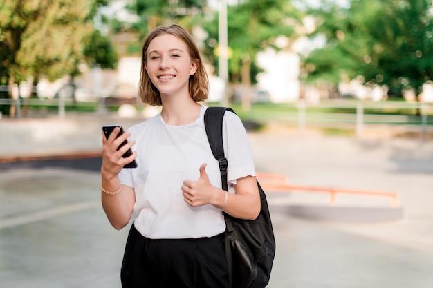 Nastoletnia studencka dziewczyna z szkolną torbą w parku